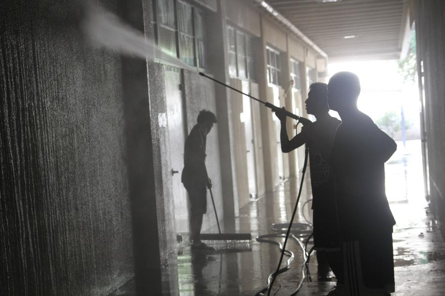 Soshi Suzuki (11) power washes a wall in building 5.
