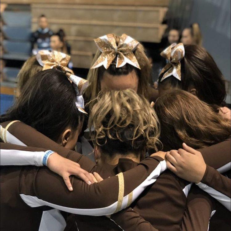 The West High Cheer Team linked arm in arm, offering each other words of encouragement before their performance. Courtesy of Eva Reyes.