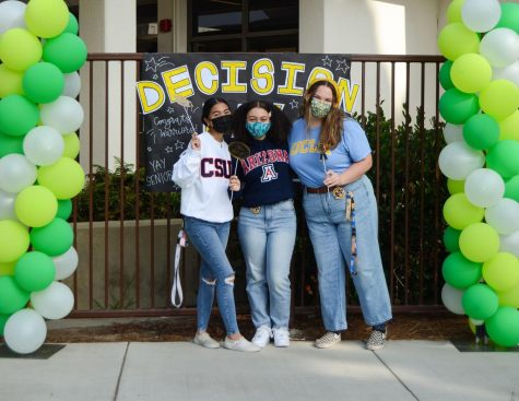 """Posing in front of a photo-op station, Daelene Cabahug (12), Lauren Bolton (12), and Faith Shortridge (12) sport college merch for Senior Decision Day. Shortridge explained how the seniors """"signed a banner, got a cool button, and had our picture taken before we got a donut and took a bunch of pictures."""" She also expressed how being able to """"talk and take pictures with everyone"""" was fun for all the seniors."""