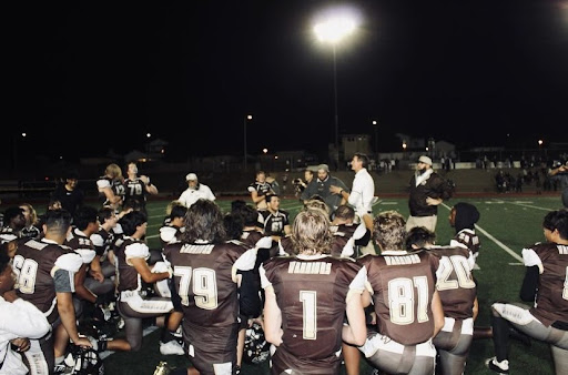 """Varsity Football takes a knee minutes before the game, receiving words of encouragement from their coach. """"Youll be fifteen years down the line and youll remember that one Homecoming game … when you have kids you will be able to tell them how it was for you,"""" Varsity player Juan Garcia (12) joyfully said."""